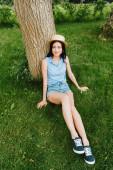 šťastná dívka v slamáku sedí na zelené trávě v blízkosti kmene stromu