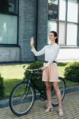 šťastná mladá podnikatelka stojící na kole a mávající rukou
