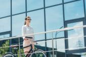 Schöne Geschäftsfrau mit Brille steht mit Fahrrad neben Gebäude