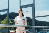 boldog üzletasszony vezeték nélküli fejhallgató gazdaság okostelefon és papír pohár közel épület
