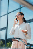 selective focus of businesswoman in glasses talking on smartphone near building and bicycle