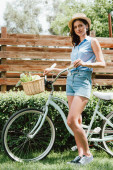 cheerful girl in straw hat standing with bicycle near fence