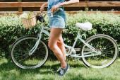 oříznutý pohled mladá žena stojící na kole v blízkosti plotu