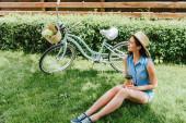 Frau mit Strohhut hält Pappbecher in der Hand und sitzt auf Gras neben Fahrrad