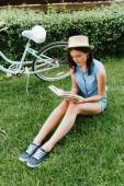 stylová žena v slamáku čtení knihy a posezení na trávě v blízkosti kola