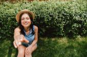 szelektív fókusz boldog lány szalma kalap kinyújtott kézzel ül közel bokor