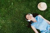 vrchol pohled na veselou ženu ležící na trávě a poslech hudby v blízkosti slamáku