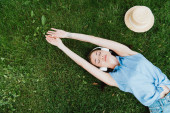 top view of attractive woman lying on grass and listening music near straw hat