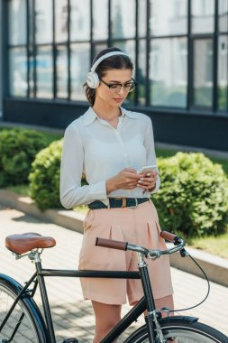 Young businesswoman in glasses listening music in wireless headphones and using smartphone near bicycle stock vector