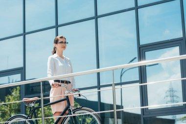 Gözlüklü güzel iş kadını binanın yanında bisikletle dikiliyor.