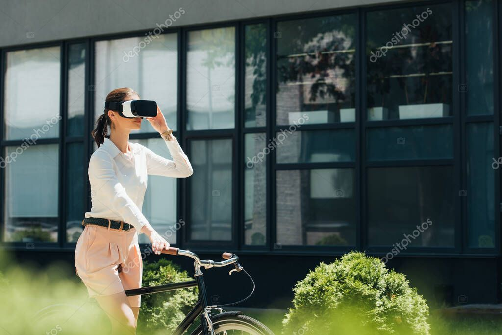 Selective focus of businesswoman in virtual reality headset riding bicycle near building stock vector