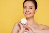 usmívající se krásná nahá žena drží kontejner s kosmetickým krémem izolované na žluté