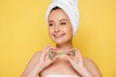 usmívající se krásná žena s ručníkem na hlavě a nefritový válec izolované na žluté