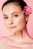 naked beautiful woman with pink lines on body and flower in hair isolated on pink