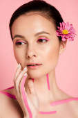 naked beautiful woman with pink lines on body and flowers in hair looking away isolated on pink