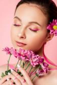 nahá krásná žena se zavřenýma očima, růžové linie na těle a květiny ve vlasech drží kytice izolované na růžové