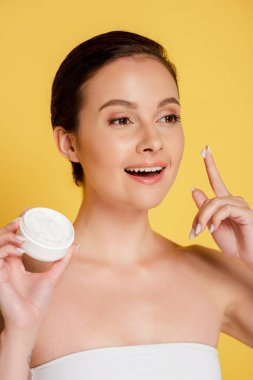Smiling beautiful woman with cosmetic cream on finger isolated on yellow stock vector