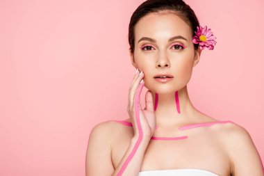 Beautiful woman with pink lines on body and flower in hair touching face isolated on pink stock vector
