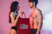Photo sexy woman holding shopping bag with sex shop lettering and looking at shirtless man on pink with smoke