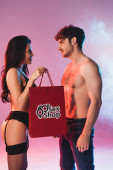 Photo side view of sexy woman holding shopping bag with sex shop lettering and looking at shirtless man on pink with smoke