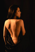 Photo side view of naked woman covered by silk bed sheet isolated on black