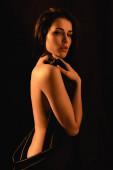 smyslná a nahá žena pokrytá hedvábnou prostěradlo izolované na černé