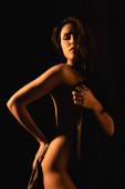 Beleuchtung einer sinnlichen und nackten Frau, die von einem seidenen Bettlaken bedeckt ist, isoliert auf schwarz