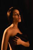 osvětlení na smyslné ženy se zavřenýma očima zabalené v hedvábné prostěradlo izolované na černé