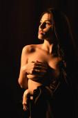 világítás érzéki nő csomagolva selyem ágynemű borító mell elszigetelt fekete