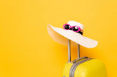 sluneční klobouk a sluneční brýle na rukojeti kufru na žlutém pozadí