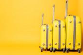 hromada cestovních tašek na žlutém pozadí