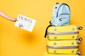Ausgeschnittene Ansicht einer Frau mit Reisezeitung in der Nähe eines blauen Rucksacks auf Reisetaschen auf gelb