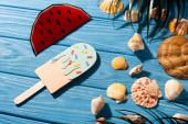 pohled shora na papírovou zmrzlinu s postřikovači a melounem v blízkosti mušlí a palmových listů na dřevěném modrém pozadí