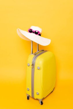 Sun hat and sunglasses on suitcase handle on yellow background stock vector