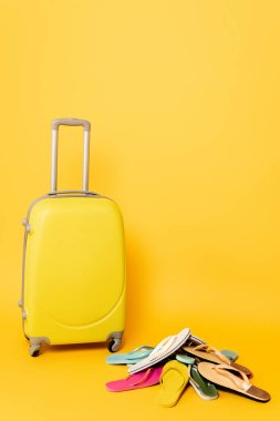 Travel bag with colorful flip flops on yellow background stock vector