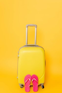 Travel bag with pink flip flops isolated on yellow background stock vector