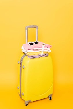 Travel bag with summer clothes and accessories isolated on yellow stock vector