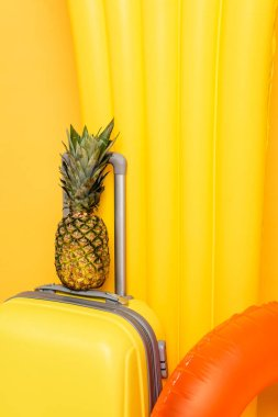 Close up view of travel bag with pineapple near pool floats on yellow background stock vector
