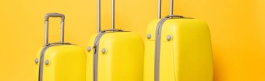 Stack of travel bags on yellow background, panoramic shot stock vector