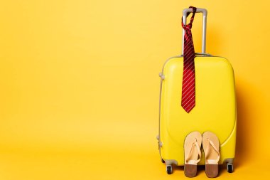 Yellow travel bag with red tie and flip flops isolated on yellow stock vector
