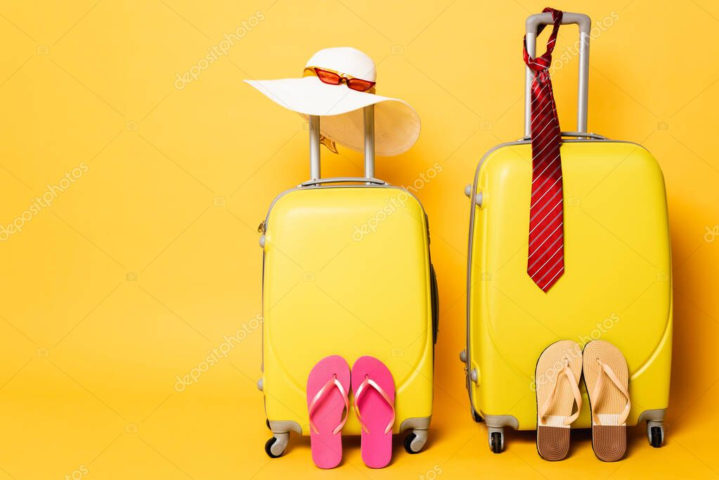 Travel bags with male and female accessories isolated on yellow stock vector