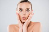 překvapená žena dotýká obličeje a oční pásky izolované na šedé