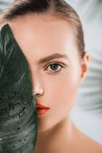atraktivní žena s make-up při pohledu na kameru v blízkosti zelené a mokré listy na bílém