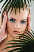 selektivní zaměření krásné ženy s modrým okem stín dotýkat tvář v blízkosti palmové listy na bílé