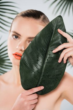 Naked woman with makeup looking at camera and covering face with green leaf on white stock vector