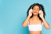 american girl with closed eyes listening music and touching wireless headphones isolated on blue