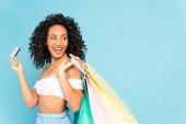 kudrnatá africká americká žena držící kreditní kartu a nákupní tašky izolované na modré
