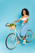 cheerful african american girl riding bicycle on blue, summer concept