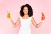 glücklich afrikanisch-amerikanische Mädchen hält Cocktails auf rosa
