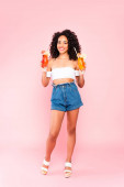 smiling african american woman standing and holding cocktails on pink